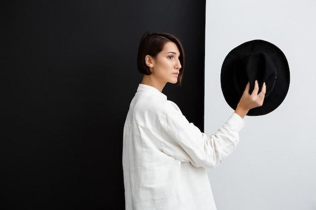 Giovane bello cappello della tenuta della ragazza sopra la parete in bianco e nero