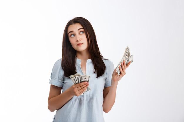 Giovane bello cercare meditatamente i soldi della tenuta della ragazza di affari sopra la parete bianca
