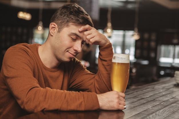 Giovane bello che beve birra al bar