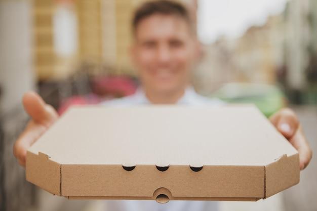Giovane bello che cammina sulla via della città con il contenitore di pizza