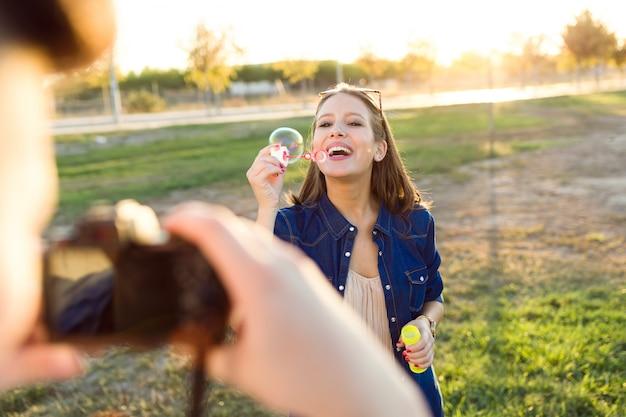 Giovane bello che cattura foto della sua ragazza che fa le bolle di sapone nel parco.