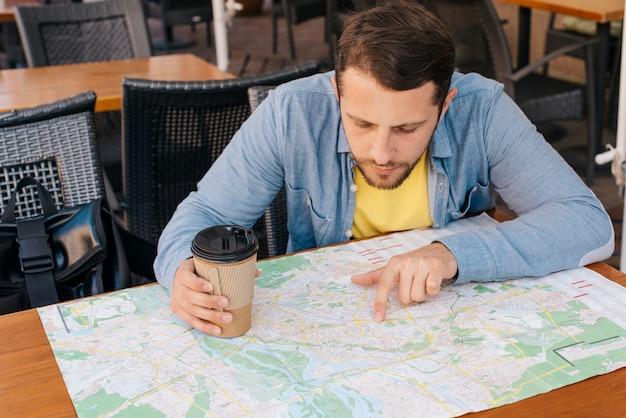 Giovane bello che esamina mappa con la tenuta della tazza di caffè nel caf?