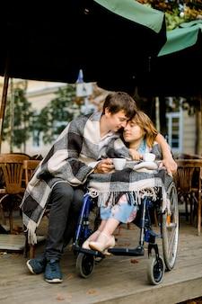Giovane bello che mangia un certo caffè e una datazione con la donna su una sedia a rotelle un giorno soleggiato