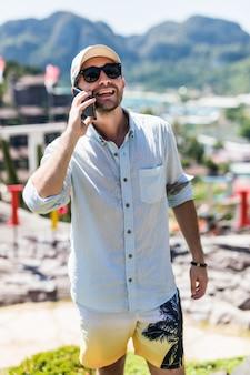 Giovane bello che parla sulla vista del telefono nel punto di vista dell'isola di phi phi. vacanze estive concetto
