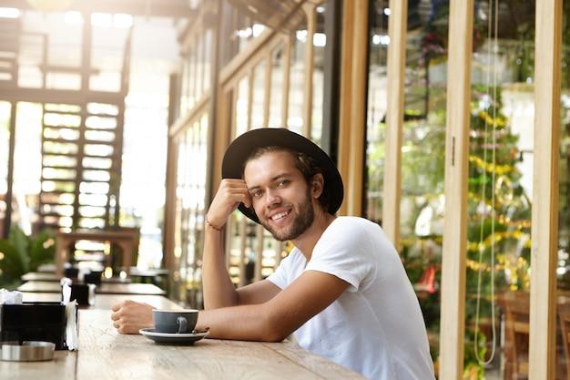 Giovane bello che porta cappello d'avanguardia che si siede alla tavola di legno della caffetteria