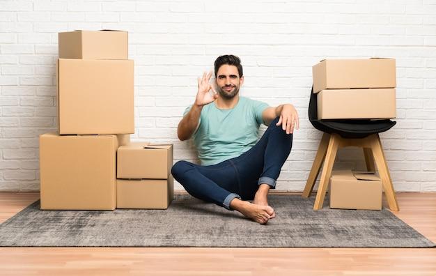 Giovane bello che si muove nella nuova casa fra le scatole che mostrano un segno giusto con le dita