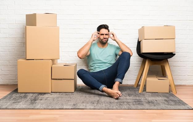 Giovane bello che si muove nella nuova casa fra le scatole infelici e frustrate con qualcosa. espressione facciale negativa