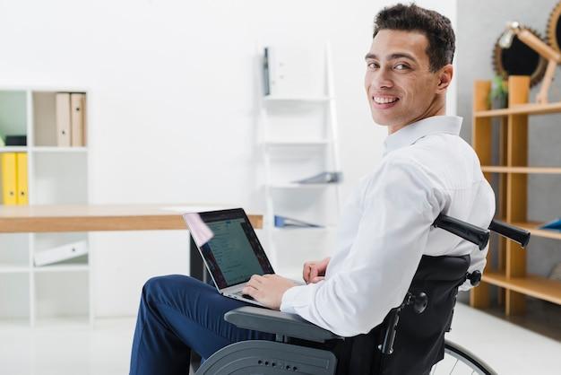 Giovane bello che si siede sulla sedia a rotelle con il computer portatile che guarda l'obbiettivo