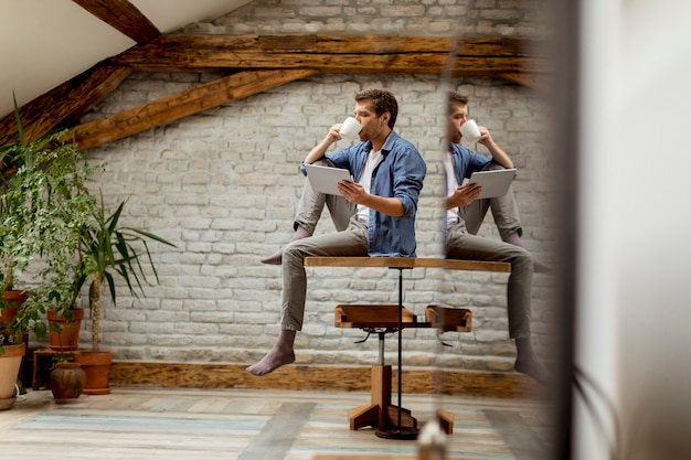 Giovane bello che utilizza compressa digitale e caffè srinking mentre sedendosi nella stanza rustica