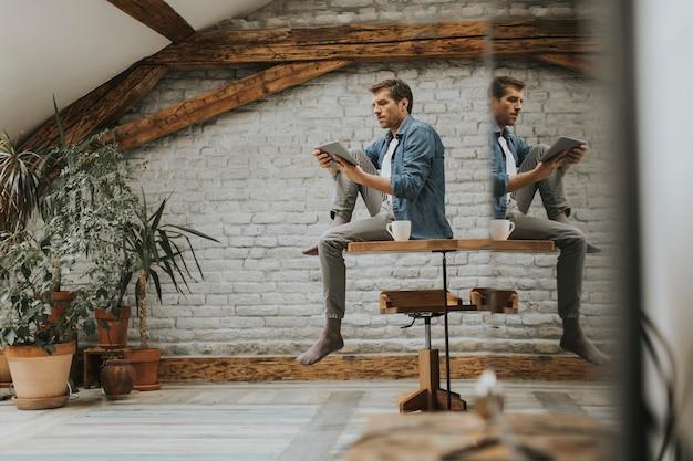 Giovane bello che utilizza compressa digitale mentre sedendosi nella stanza rustica