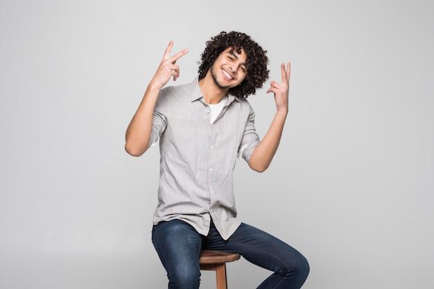 Giovane bello con capelli ricci che si siedono sulla sedia sopra la parete bianca