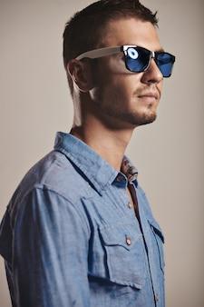 Giovane bello con gli occhiali da sole alla moda in studio