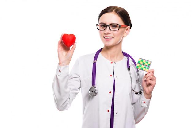 Giovane bello cuore e pillole femminili della tenuta di medico in sue mani su fondo bianco
