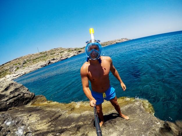 Giovane bello e attivo nella maschera per lo snorkeling sta facendo un selfie.