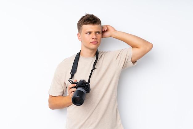 Giovane bello fondo bianco con una macchina fotografica e un pensiero professionali