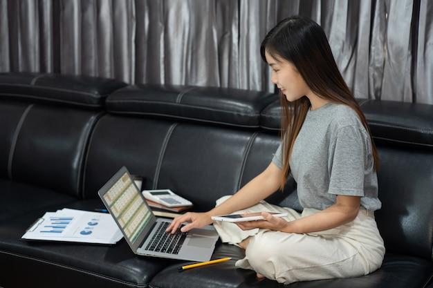 Giovane bello imprenditore asiatico attraente o libero professionista della donna che lavora a casa con le relazioni di attività del computer portatile e le comunicazioni online sul sofà del salone, funzionante a distanza accede al concetto.