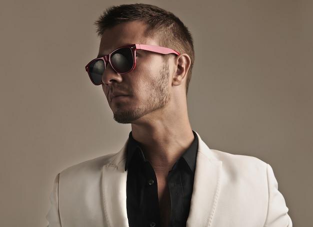 Giovane bello in vestito bianco con gli occhiali da sole alla moda