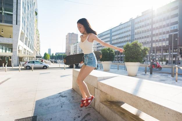 Giovane bello pattinatore lungo asiatico diritto della donna dei capelli diritti che salta giù da una piccola parete