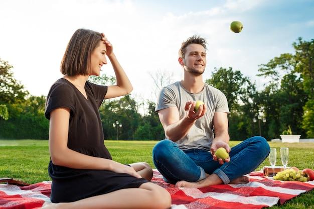 Giovane bello picnic del restingon delle coppie al parco.