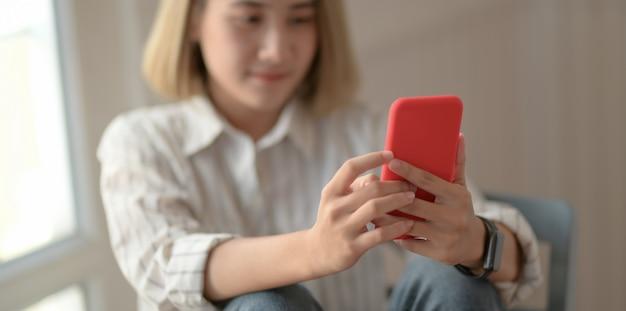 Giovane bello progettista femminile che esamina smartphone e che si siede sulla sedia