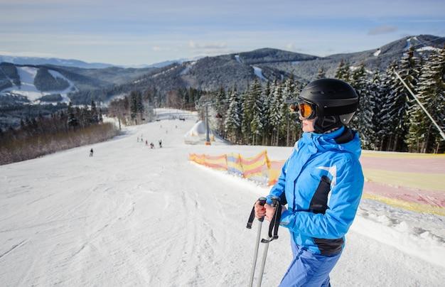 Giovane bello sciatore femminile nel mezzo della pista da sci