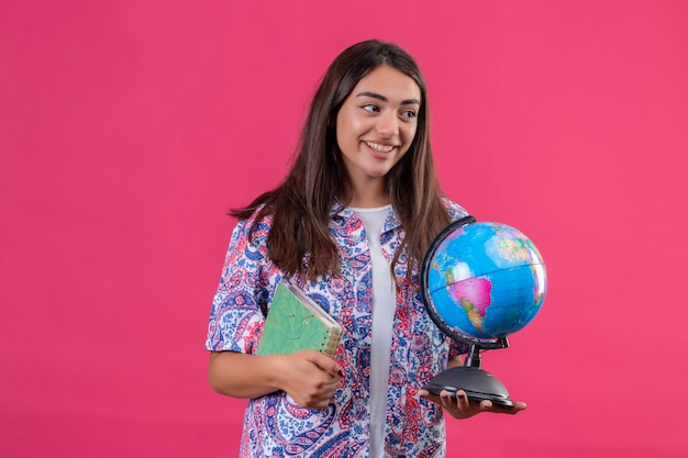 Giovane bello taccuino e globo della tenuta della donna del viaggiatore che guardano da parte con il fronte felice che sorride sopra la parete rosa isolata