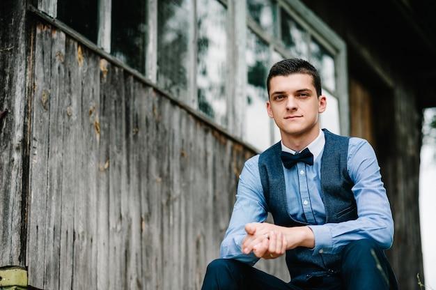 Giovane bello uomo del ritratto che si siede accanto alla parete di legno di vecchia casa