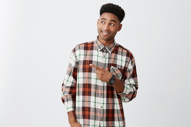 Giovane bello uomo di colore allegro con l'acconciatura afro in camicia casuale alla moda che sorride con i denti, indicando sullo spazio libero, guardando da parte con espressione eccitata e delizia