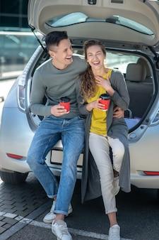 Giovane bello uomo e donna che beve caffè vicino a un'auto