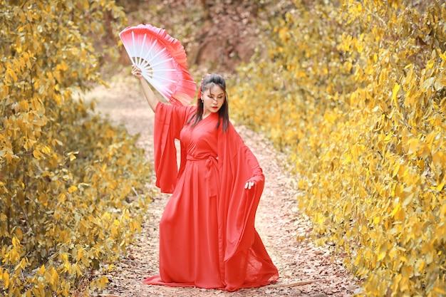 Giovane bello vestito asiatico dalla donna nello stile tradizionale del guerriero di vecchio modo del cinese con il fan antico. donna carina in abito rosso in piedi e guardando lontano.