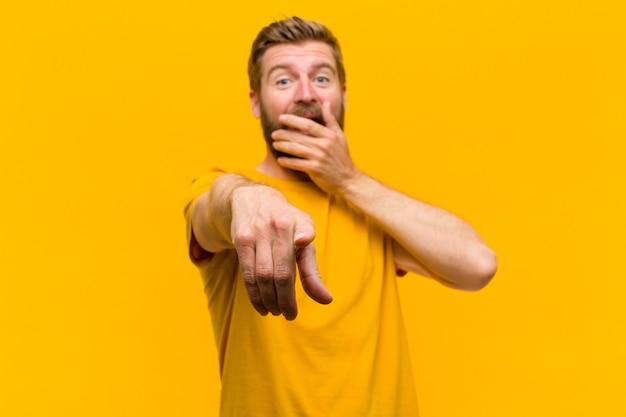 Giovane bionda che ride di te, indicando la fotocamera e prendendo in giro o deridendoti contro il muro arancione