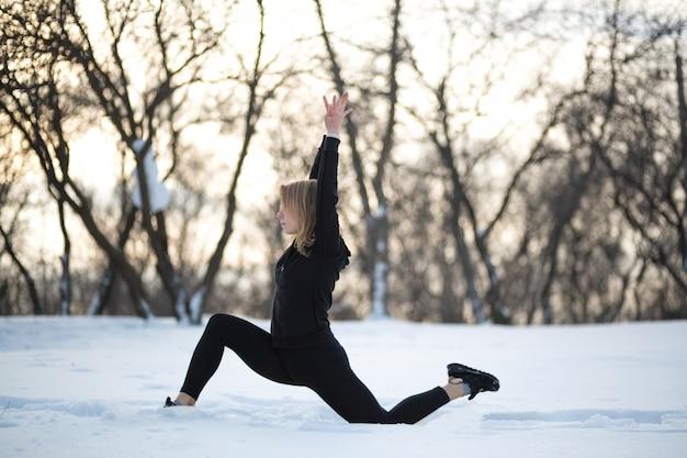Giovane bionda femmina caucasica in ghette allungando esercizio all'aria aperta nella foresta nevosa.