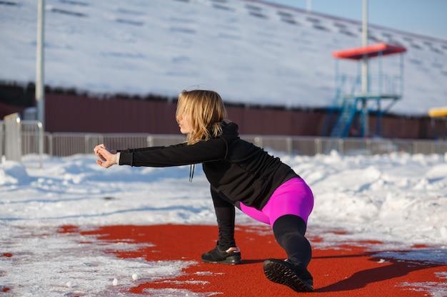 Giovane bionda femminile in ghette viola che allungano esercizio su una pista da corsa rossa in uno stadio innevato.