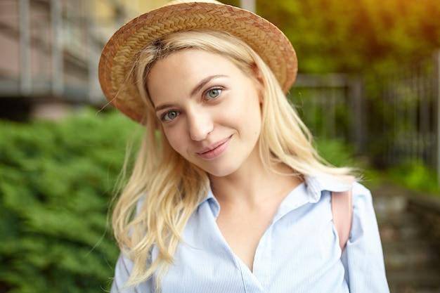 Giovane bionda studente in un cappello di paglia in piedi sulla parte anteriore dell'università.
