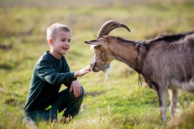 Giovane biondo carino bel ragazzo sorridente bambino che gioca con la capra cornuta barbuta all'aperto in estate soleggiata luminosa o primavera su sfocato verde chiaro erboso