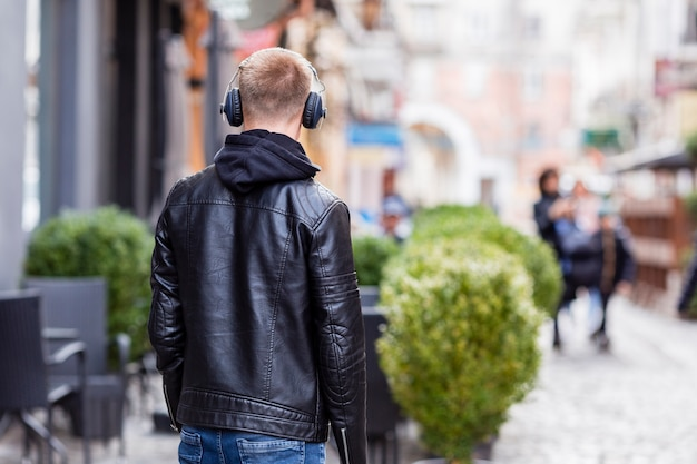 Giovane biondo di vista posteriore che ascolta la musica sulle cuffie