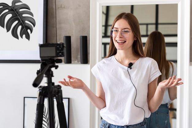 Giovane blogger che registra con videocamera e microfono professionali