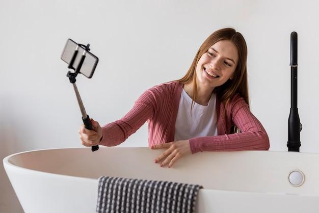 Giovane blogger che sorride e che prende un selfie