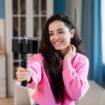 Giovane blogger felice che usando il bastone e la posa del selfie