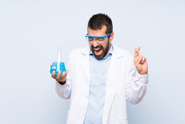 Giovane boccetta scientifica del laboratorio della tenuta con l'incrocio delle dita