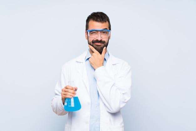 Giovane boccetta scientifica del laboratorio della tenuta sopra il pensiero isolato della parete