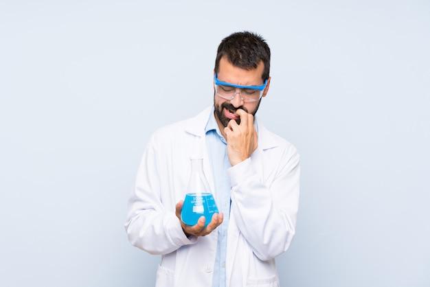 Giovane boccetta scientifica del laboratorio della tenuta sopra isolato avendo dubbi