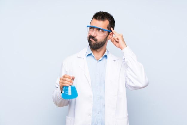 Giovane boccetta scientifica del laboratorio della tenuta sopra la parete isolata che ha dubbi e pensare