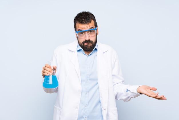 Giovane boccetta scientifica del laboratorio della tenuta sopra la parete isolata che ha dubbi mentre sollevando le mani