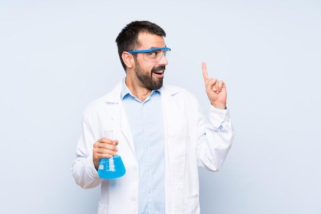 Giovane boccetta scientifica del laboratorio della tenuta sopra la parete isolata che pensa un'idea che indica il dito su