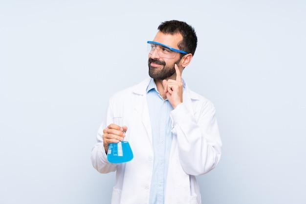 Giovane boccetta scientifica del laboratorio della tenuta sopra la parete isolata che pensa un'idea mentre cercando