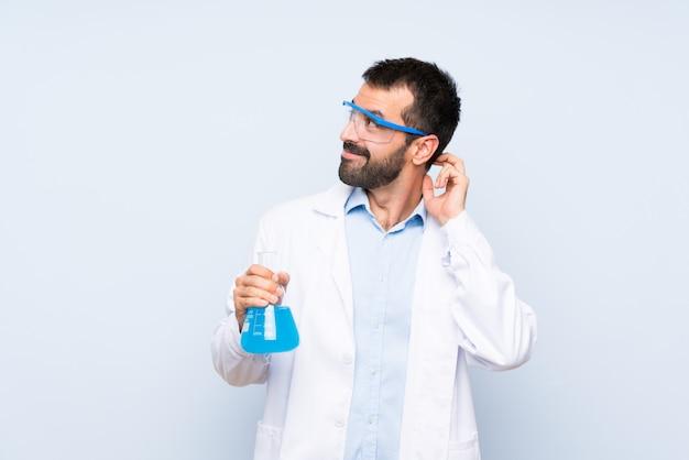 Giovane boccetta scientifica del laboratorio della tenuta sopra la parete isolata che pensa un'idea