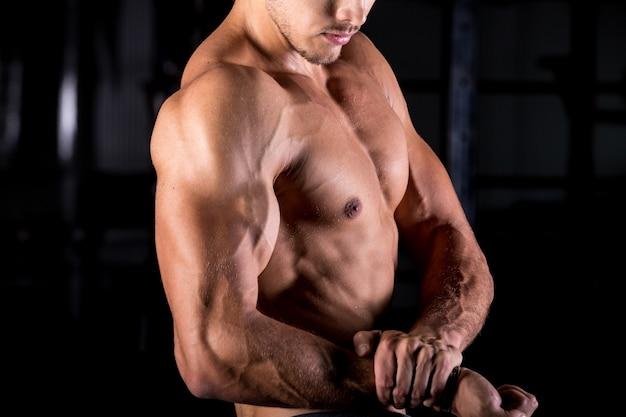 Giovane bodybuilder con le braccia muscolari