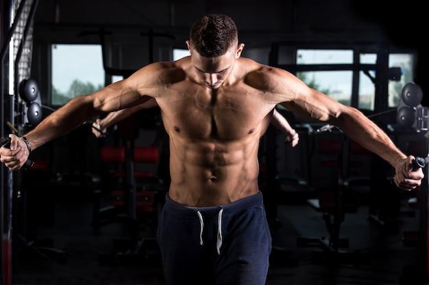 Giovane bodybuilder utilizzando attrezzature fitness