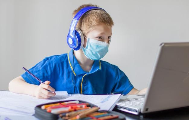Giovane bopy che studia i compiti di matematica durante la sua lezione online a casa, distanza sociale durante la quarantena, auto-isolamento, concetto di istruzione online, scuola a casa